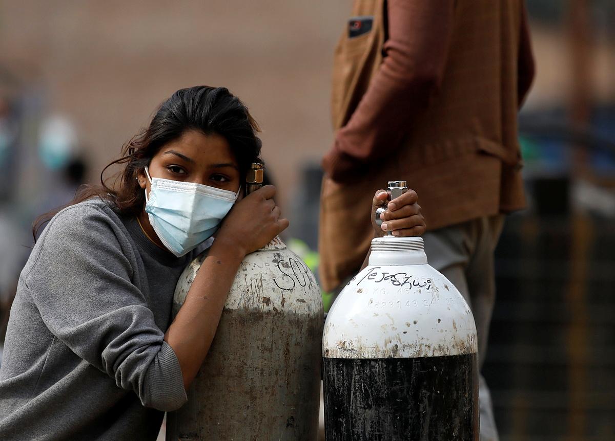 Một phụ nữ giữ hai bình oxy cho người thân mắc Covid-19 tại thành phố Kathmandu, Nepal, ngày 9/5. Ảnh: Reuters