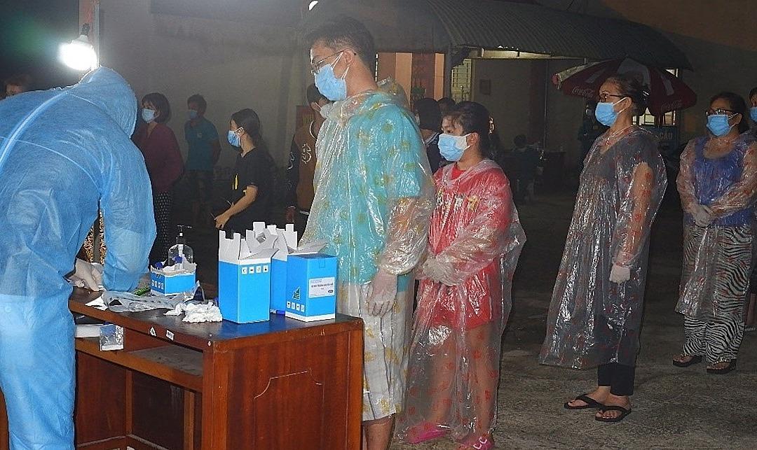 [Caption]Nhân viên y tế lấy mẫu xét nghiệm cho toàn dân phường 9, quận Gò Vấp, đêm 29/5. Ảnh: Trung tâm Kiểm soát Bệnh tật TP HCM.