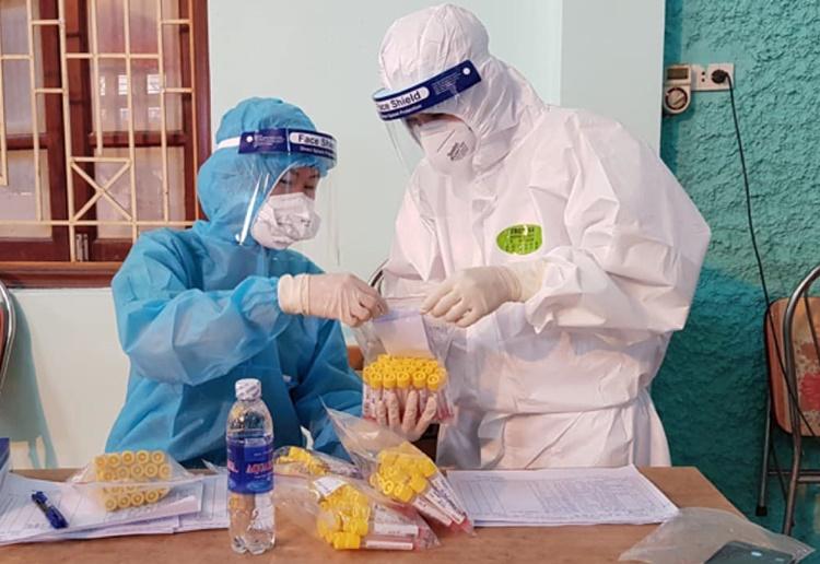 Nhân viên y tế đội chi viện Bệnh viện Việt Nam - Thụ Điển Uông Bí Quảng Ninh tiến hành lấy mẫu và phân lọa mẫu bệnh phẩm. Ảnh: Bộ Y tế cung cấp