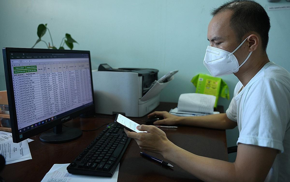 Bác sĩ Nguyễn Văn Dưỡng đang tiếp tục hoàn thiện phần mềm nhập liệu bệnh nhân sau một ngày làm việc tại khu điều trị F0. Ảnh: Hoàng Hiệp