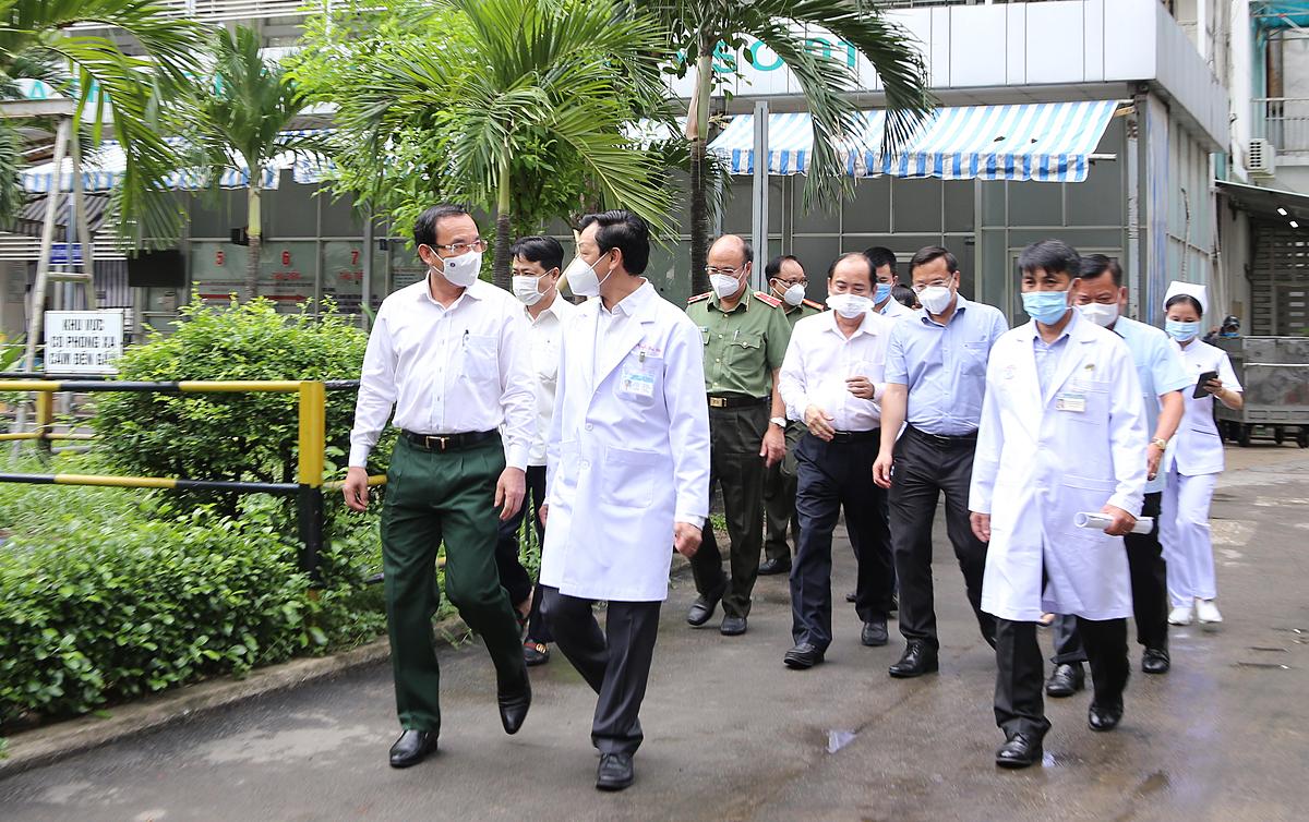 Bí thư Thành ủy TP.HCM Nguyễn Văn Nên (bìa trái) thăm, động viên đội ngũ y bác sĩ Bệnh viện Chợ Rẫy và thăm chiến sĩ công an