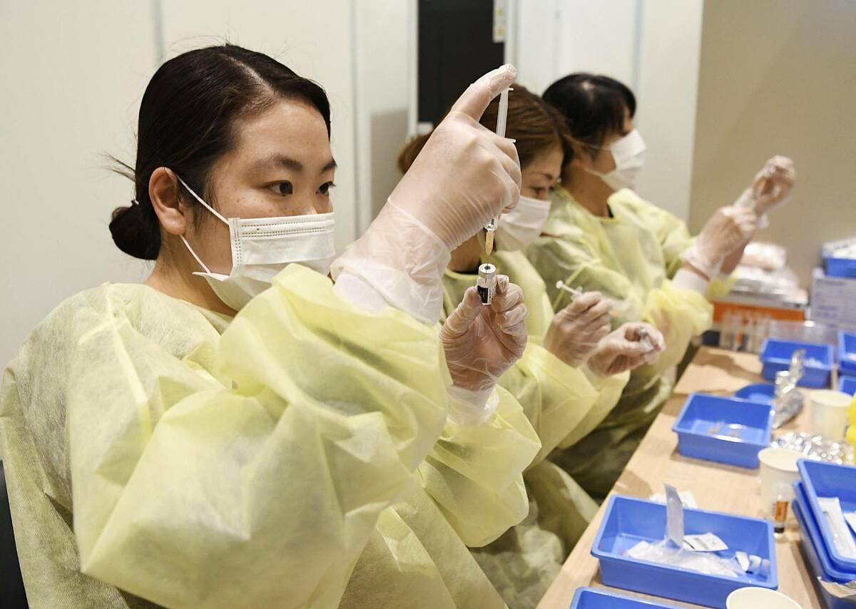 Chuyên viên tại hãng dược Shionogi chuẩn bị vaccine Covid-19 thử nghiệm lâm sàng tại Kobe, ngày 11/5. Ảnh: Kyodo