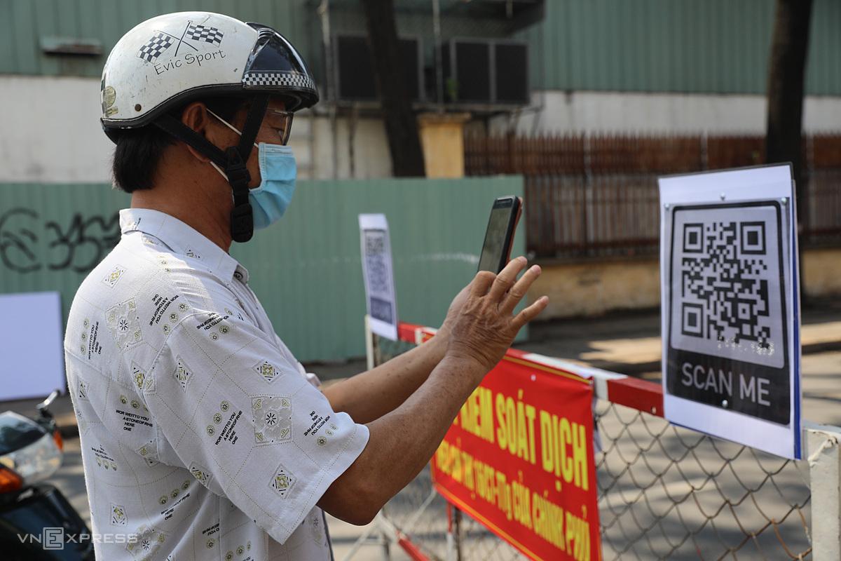Người dân khai báo y tế tại chốt kiểm soát Covid-19 trên đường Nguyễn Kiệm ở quận Gò Vấp, ngày 3/6. Ảnh: Quỳnh Trần.