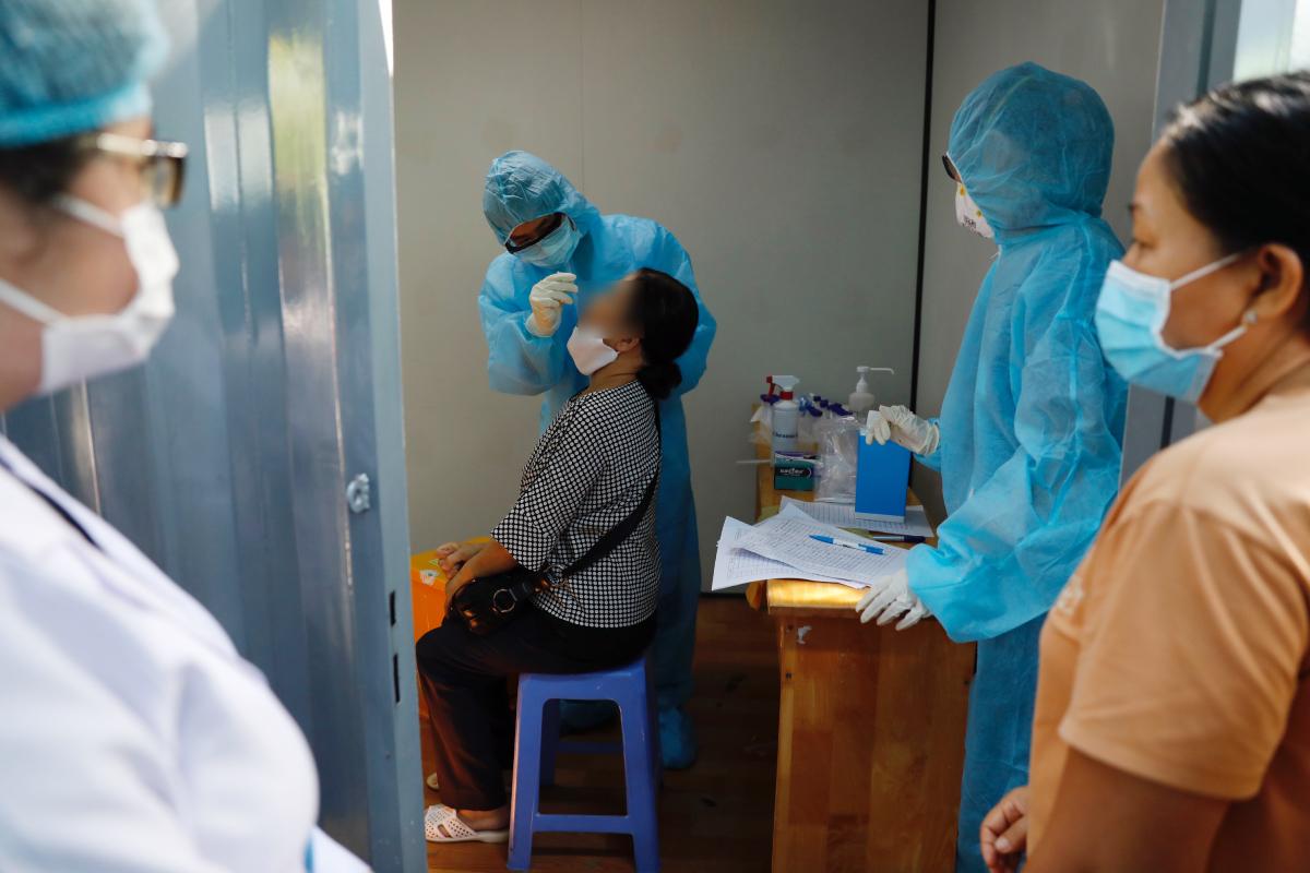 TP HCM từng triển khai xét nghiệm nCoV khẩn cấp cho tất cả nhân viên y tế cùng bệnh nhân nội trú và người nuôi bệnh tại các cơ sở y tế trên địa bàn. Trong ảnh là nhân viên y tế Bệnh viện TP Thủ Đức lấy mẫu dịch hầu họng cho một thân nhân người bệnh, ngày 13/5. Ảnh: Hữu Khoa.