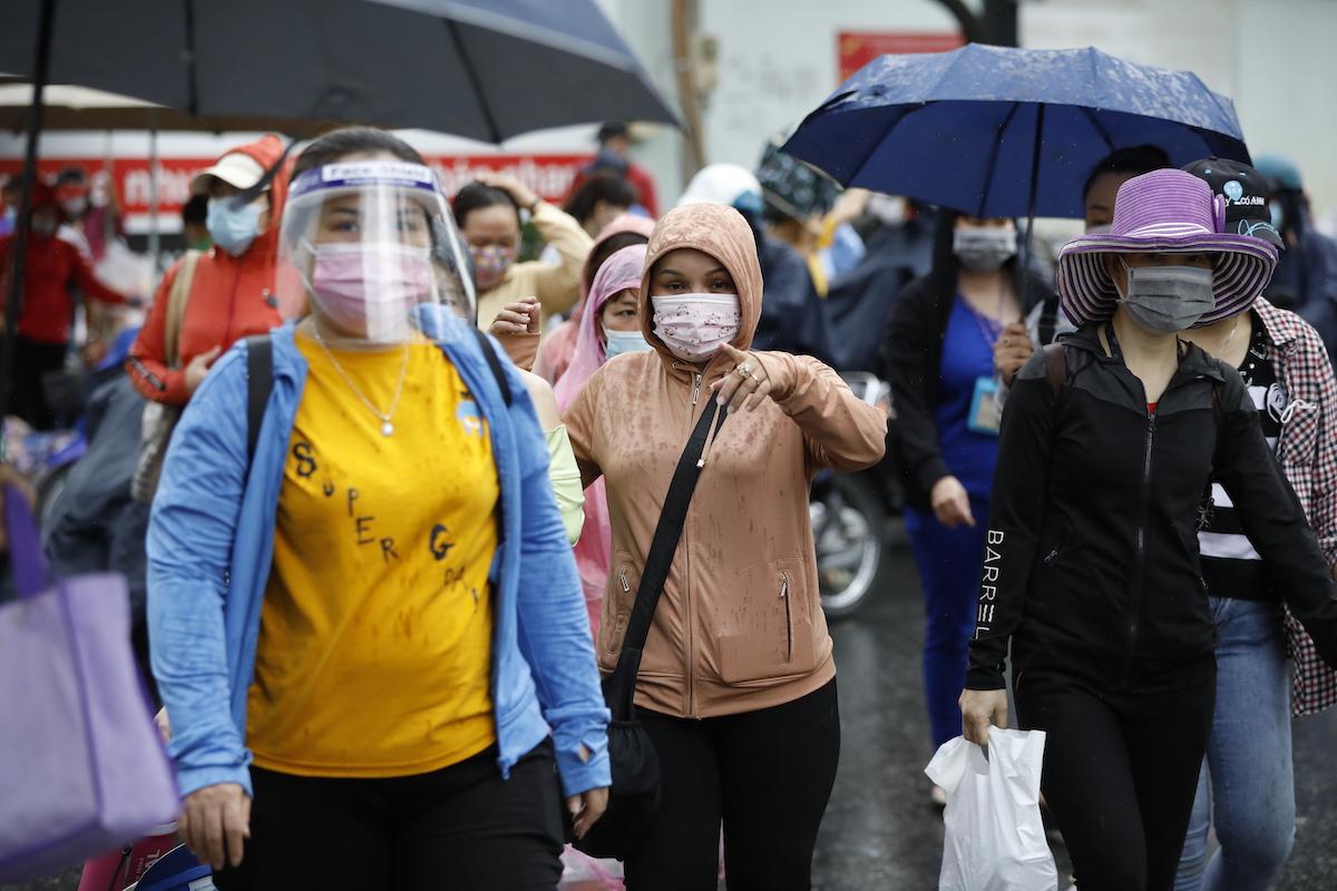 Sau khi phát hiện ca nghi nhiễm trong công ty, các công nhân ý thức mang khẩu trang đầy đủ và mặt nạ chống dịch khi tan ca, hiện 1.100 công nhân đang tạm nghỉ việc. Ảnh: Hữu Khoa