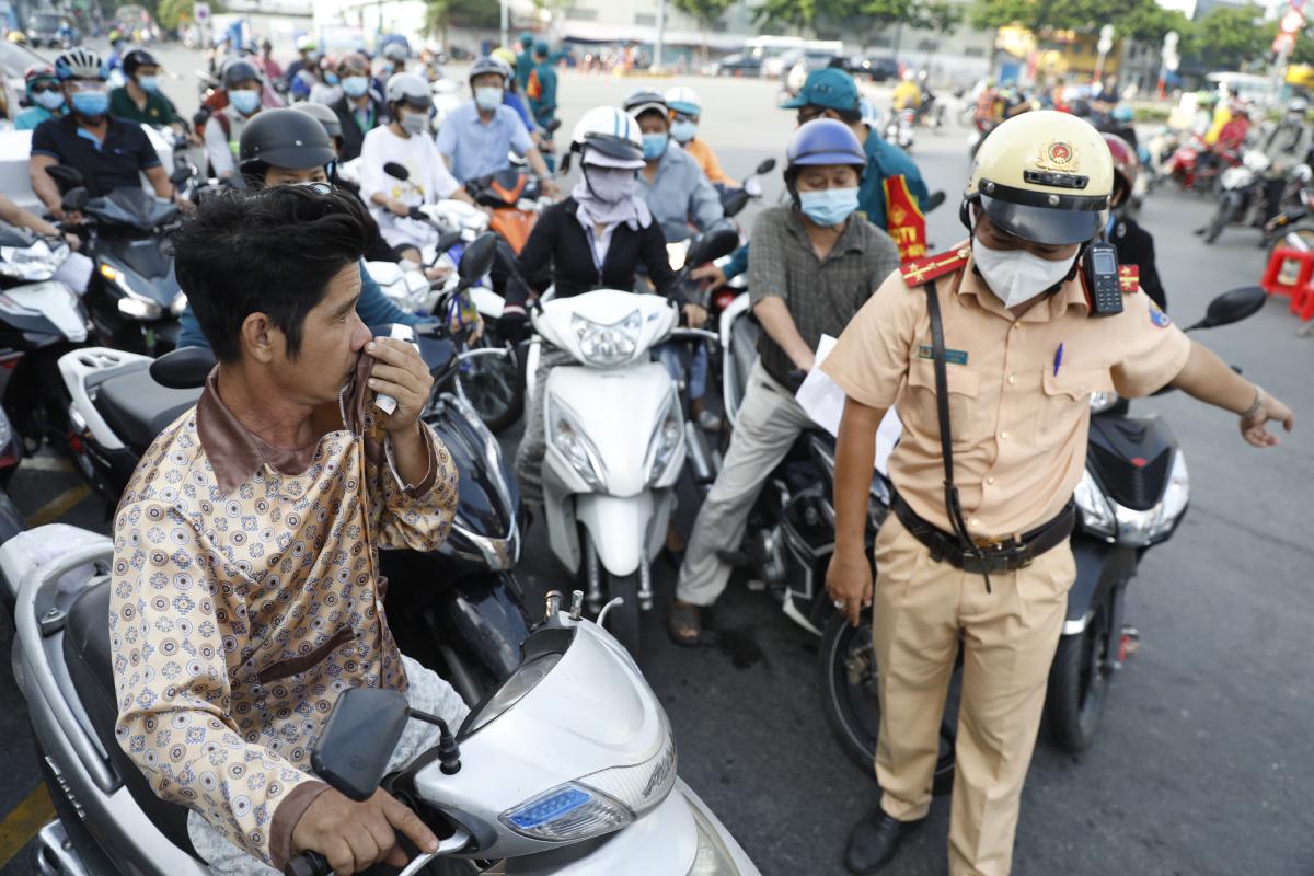 Một người đàn ông không đội mũ bảo hiểm, không đeo khẩu trang tại chốt kiểm dịch quận Gò Vấp được cảnh sát giao thông yêu cầu ngưng tham gia giao thông, ngày 1/6. Ảnh: Hữu Khoa.