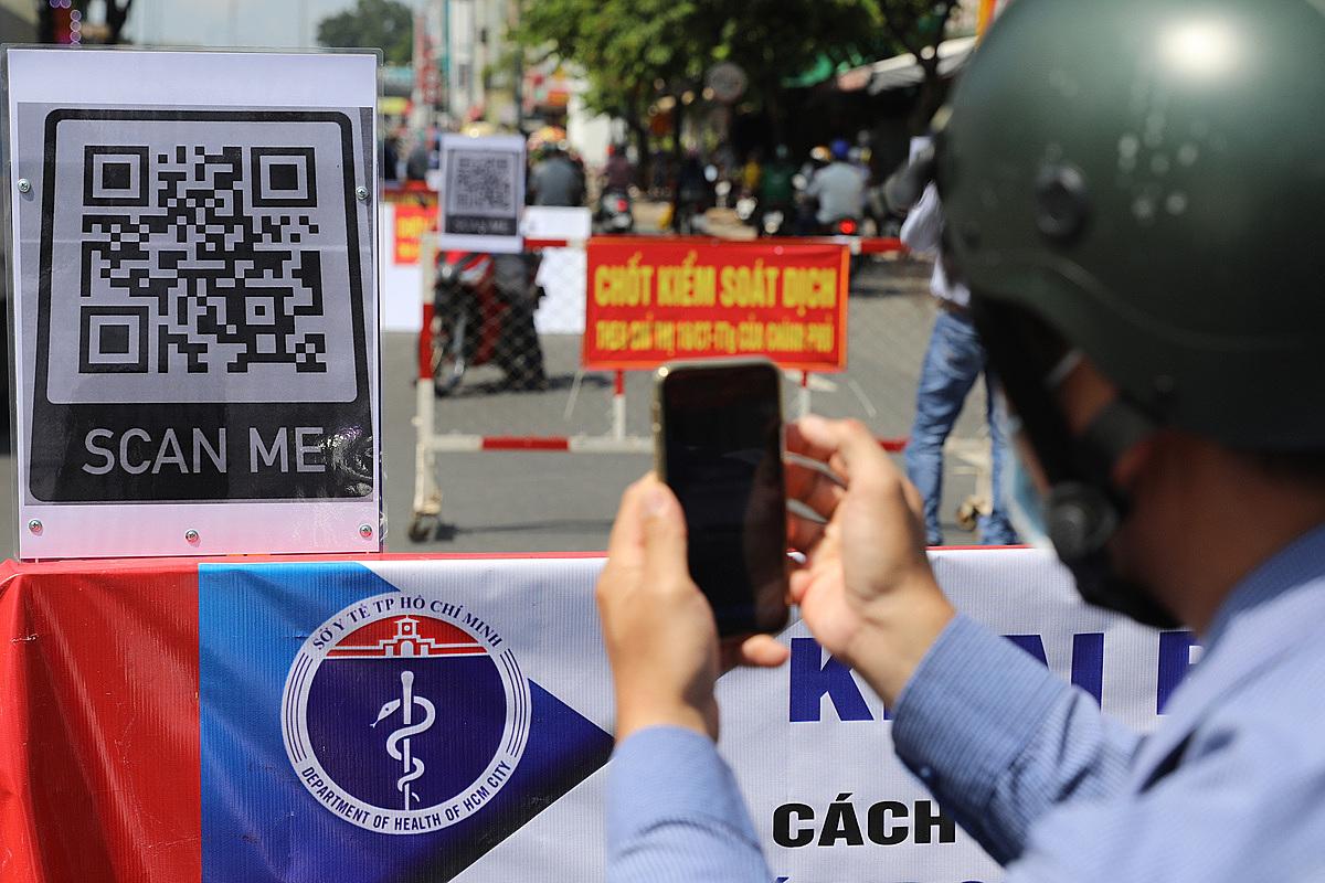 Người dân quét mã QR khai báo y tế điện tử tại chốt kiểm dịch y tế trên đường Nguyễn Kiệm, quận Gò Vấp, ngày 3/6. Ảnh: Quỳnh Trần.
