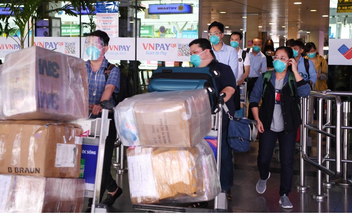 Thành viên đội phản ứng nhanh đẩy hành lý, thiết bị về thẳng Bệnh viện Chợ Rẫy từ sân bay Tân Sơn Nhất, ngày 15/6. Ảnh: Bệnh viện cung cấp.