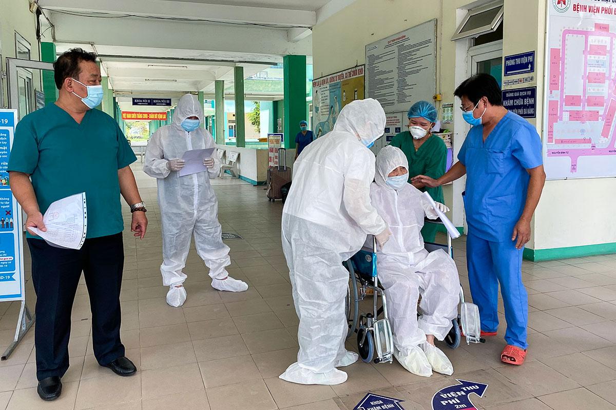 Bệnh nhân 3221 (ngồi xe lăn) được các bác sĩ hỗ trợ để di chuyển về nhà sau khi xuất viện. Ảnh: Vân Đông.