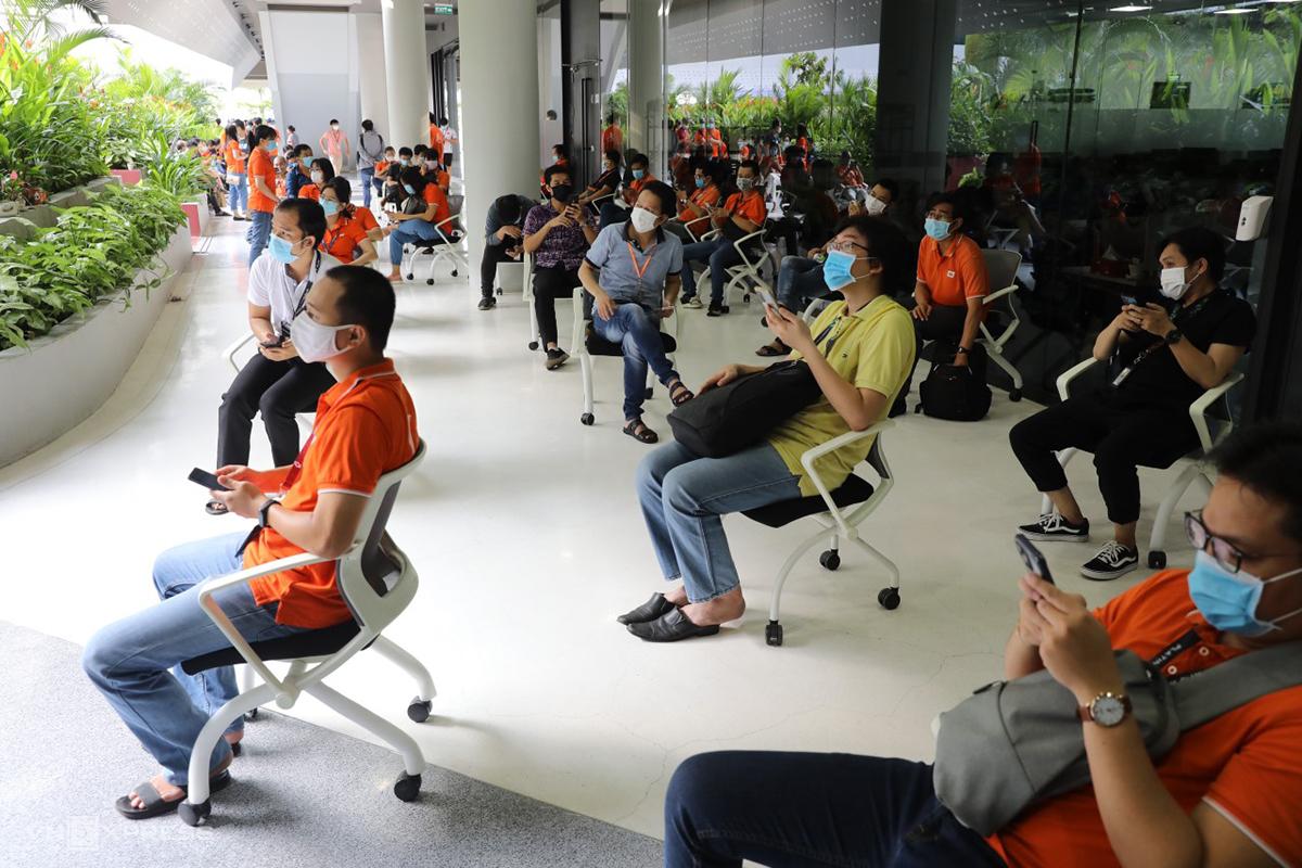 Nhân viên FPT Software ngồi giãn cách chờ đến lượt tiêm vaccine Covid-19, sáng 19/6. Ảnh: Quỳnh Trần.