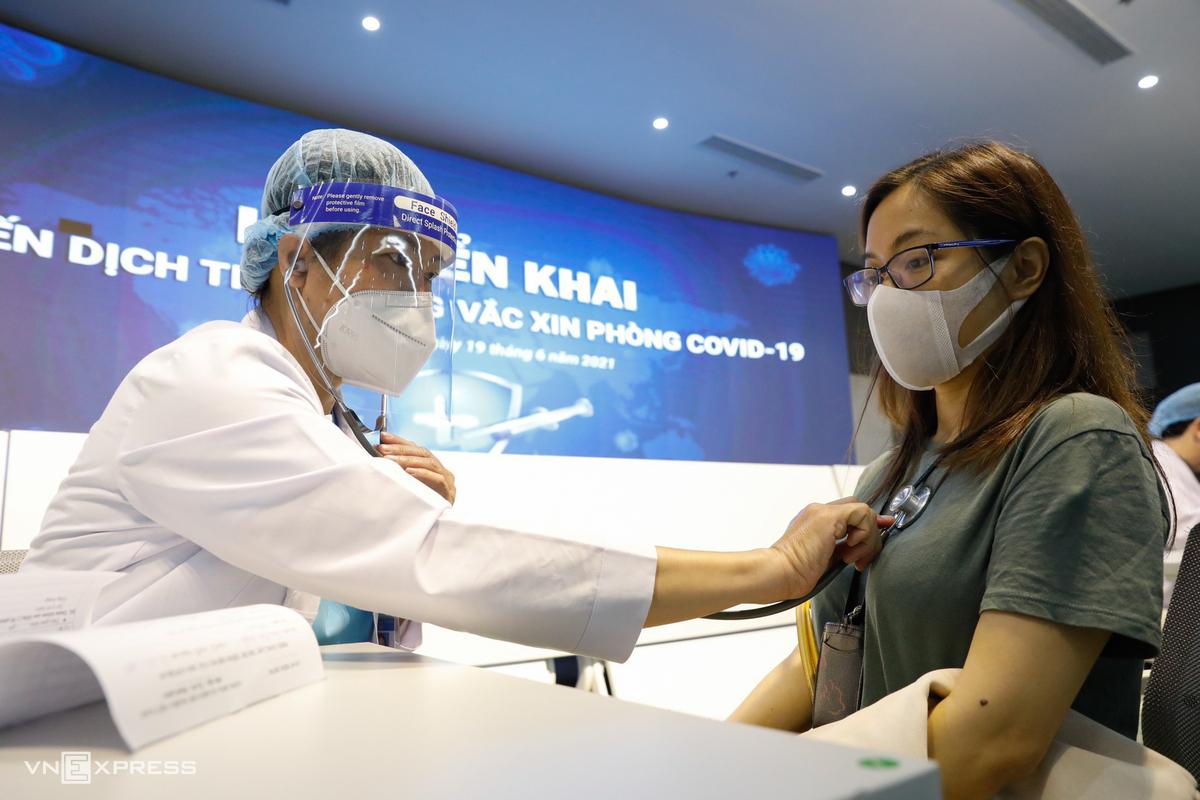Nhân viên y tế khám sức khỏe cho người tiêm vaccine. Ảnh: Quỳnh Trần