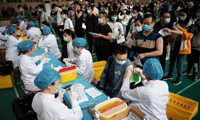 Các sinh viên đại học xếp hàng để tiêm vaccine Covid-19 tại Vũ Hán, tỉnh Hồ Bắc, Trung Quốc, hôm 28/4. Ảnh: AFP.