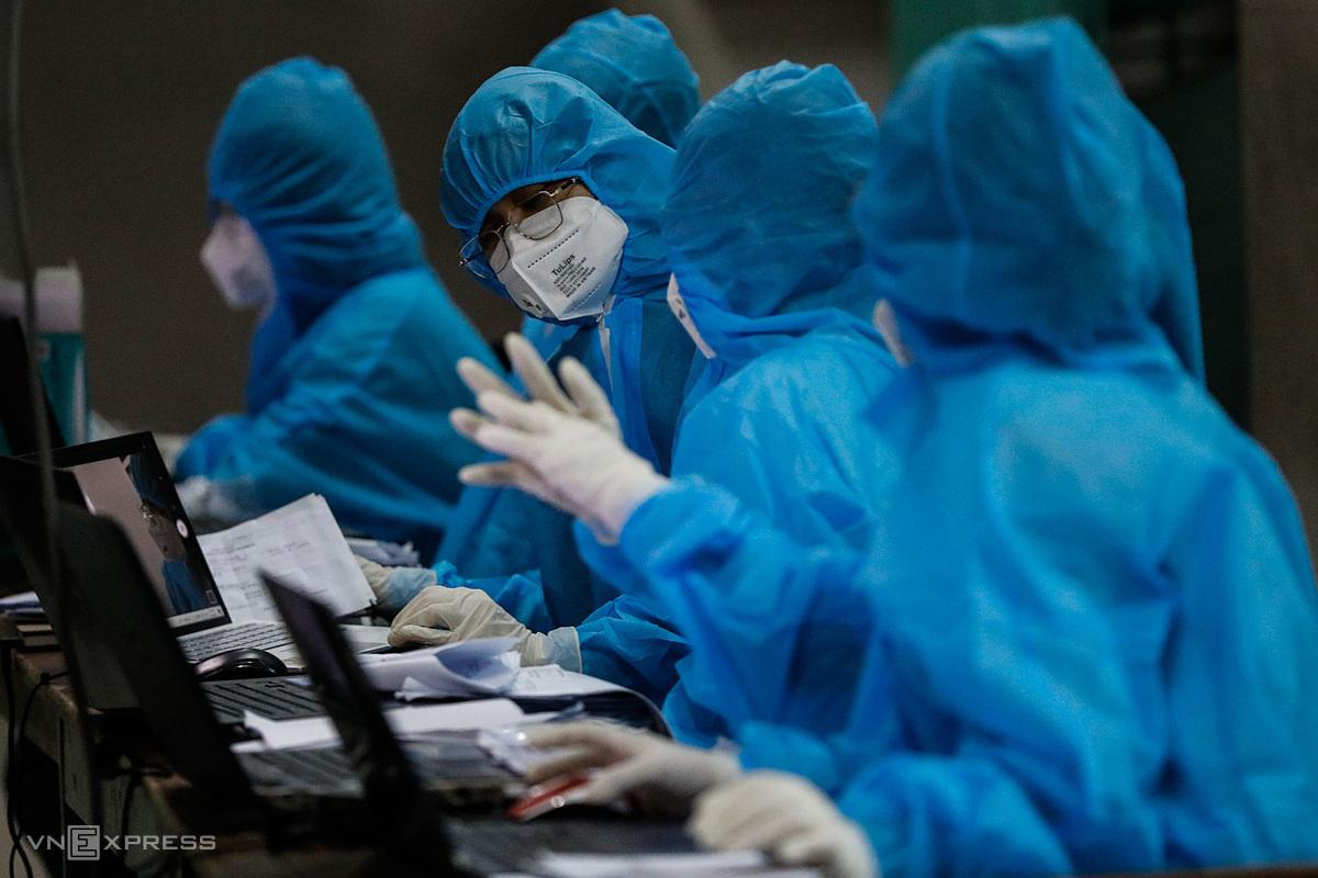 Nhân viên y tế lấy mẫu xét nghiệm Covid-19 ở quận Bình Tân, đêm 22/6. Ảnh: Hữu Khoa.