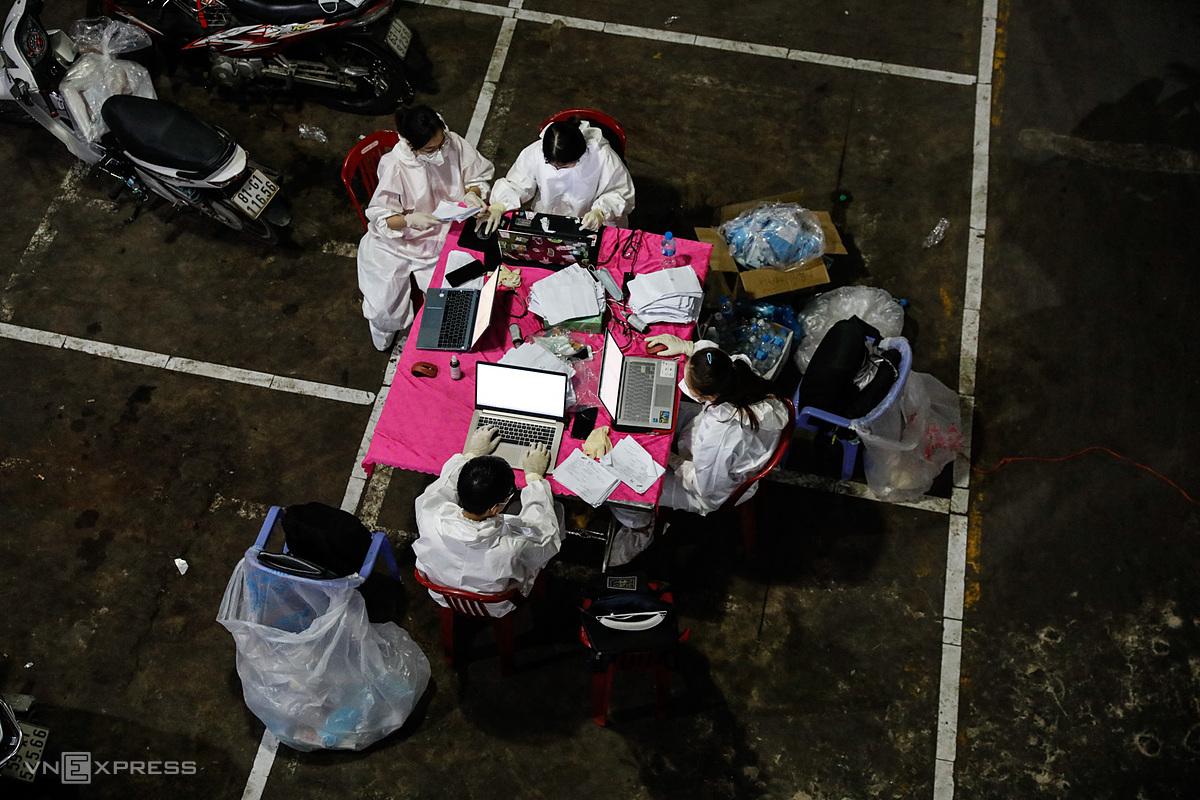 Nhân viên y tế lấy mẫu xét nghiệm tại quận Bình Tân, đêm 22/6. Ảnh: Hữu Khoa.