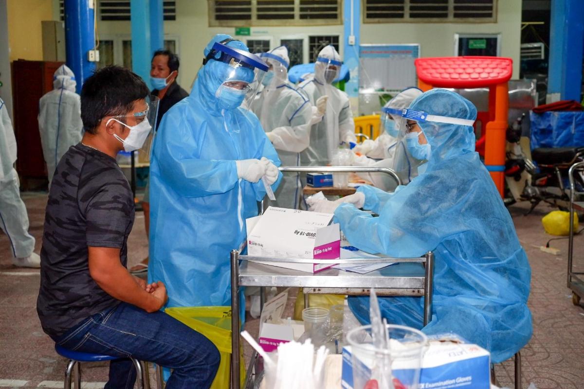 Nhân viên y tế lấy mẫu xét nghiệm cho người dân khu vực chợ Sơn Kỳ, tối 23/6. Ảnh: HCDC.