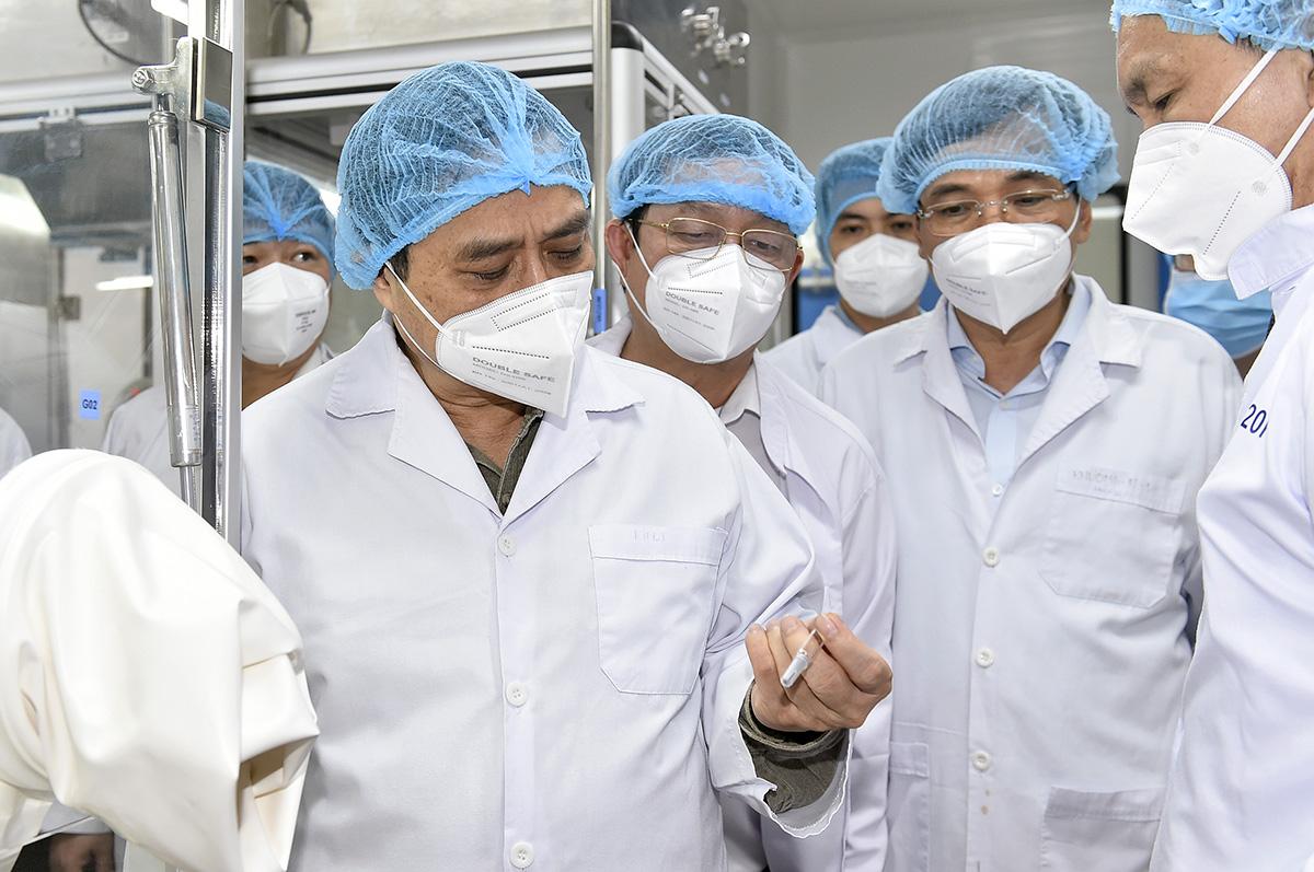 Thủ tướng xem công nghệ đóng lọ vaccine có sẵn kim tiêm. Ảnh: VGP.
