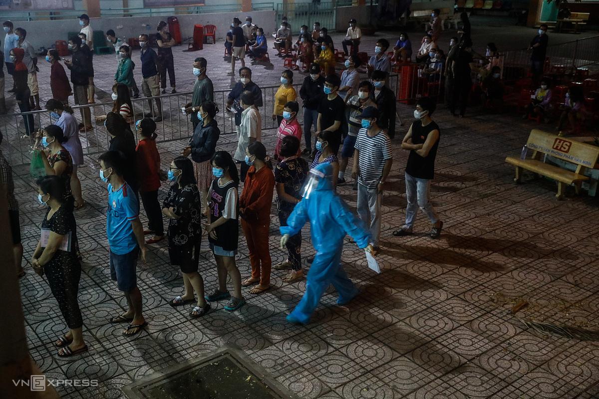 Lấy mẫu xét nghiệm Covid-19 ở quận Bình Tân, đêm 22/6. Ảnh: Hữu Khoa.