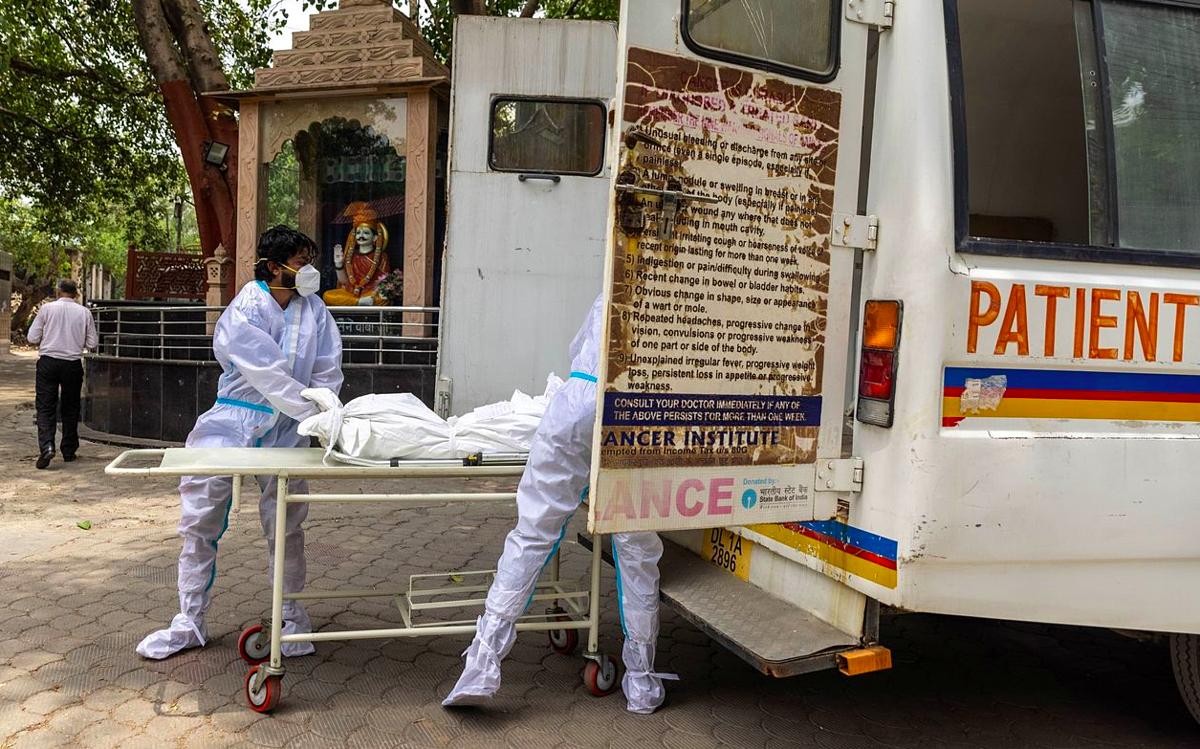 Nhân viên y tế chuyển thi thể một bệnh nhân Covid-19 đến lò hoả táng tại New Delhi, tháng 5/2021. Ảnh: Reuters
