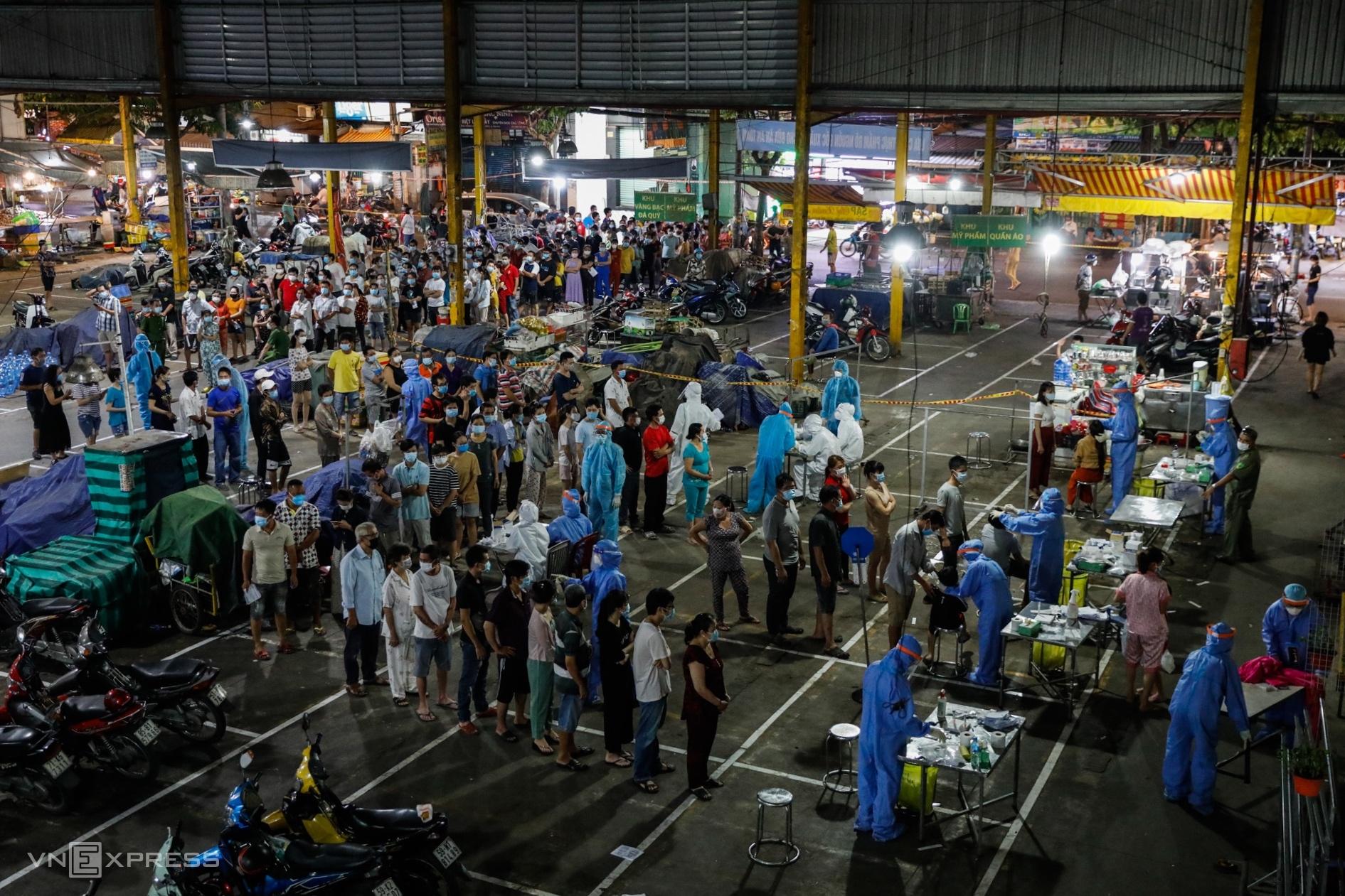Người dân quận Bình Tân chờ lấy mẫu xét nghiệm sàng lọc nCoV, đêm 22/6. Ảnh: Hữu Khoa.