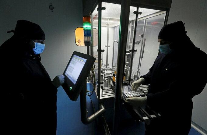 Các kỹ thuật viện làm việc trong dây chuyền sản xuất thuốc remdesivir. Ảnh: Reuters