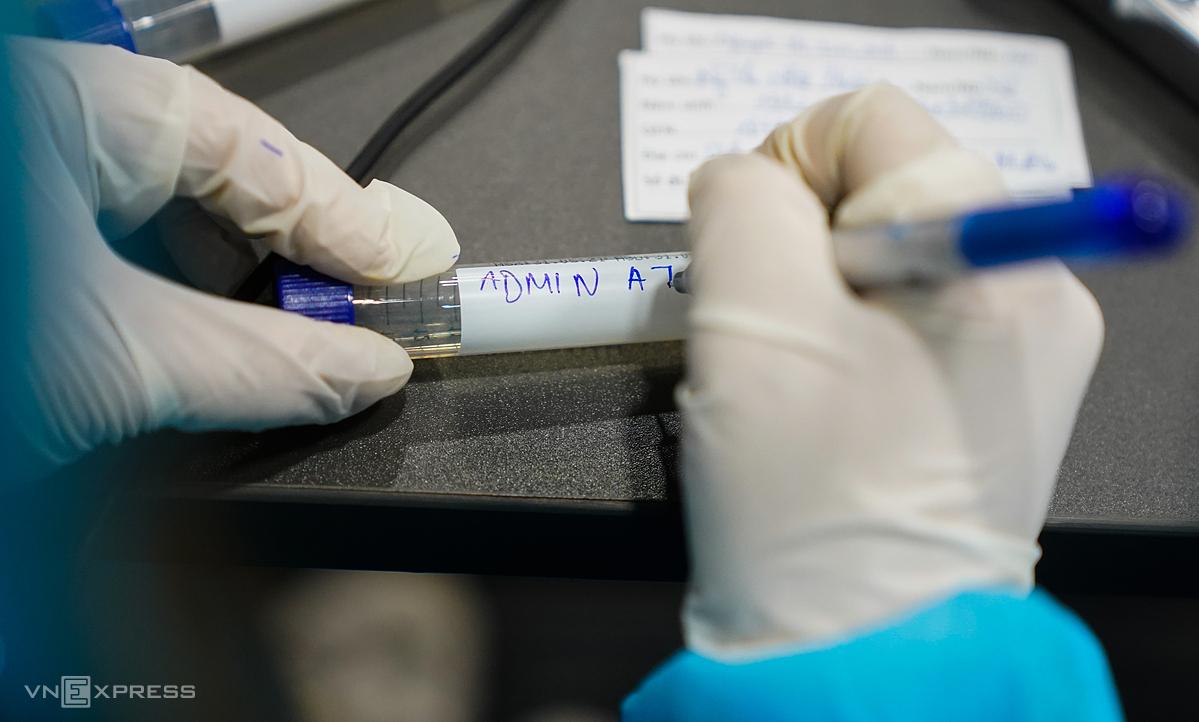 Nhân viên y tế kiểm tra thông tin công nhân lấy mẫu xét nghiệm Covid-19 tại công ty thuộc Khu công nghệ cao TP HCM, đầu tháng 6. Ảnh: Hữu Khoa.
