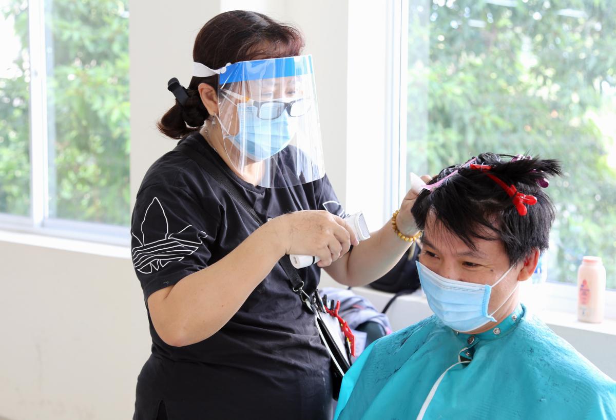 Tình nguyện viên đeo kính chắn giọt bắn, khẩu trang cắt tóc cho nhân viên y tế Bệnh viện Chợ Rẫy. Ảnh: Bệnh viện cung cấp.