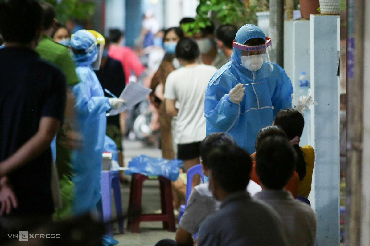 Nhân viên y tế lấy mẫu xét nghiệm cho người dân tại kiệt 20/hẻm 11 đường Hoàng Hoa Thám, lúc 20h ngày 10/7. Ảnh: Nguyễn Đông.