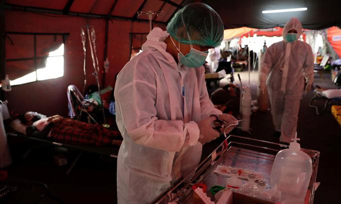 Nhân viên y tế chuẩn chăm sóc cho bệnh nhân ở lều dựng tạm bên bên ngoài khu cấp cứu bệnh viện tại Bekasi, ngoại ô Jakarta hôm 25/6. Ảnh: Reuters.