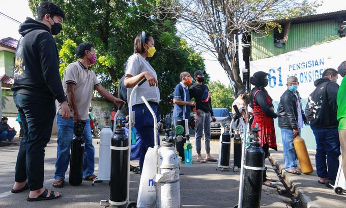 Người dân đứng chờ nạp bình oxy bên ngoài một nhà máy ở Jakarta, Indonesia, hôm 12/7. Ảnh: Reuters.
