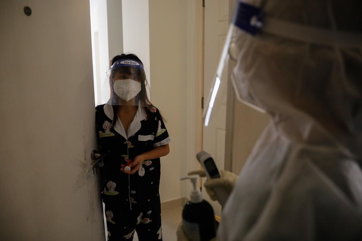 Nhân viên y tế đến phòng một F0 tại Bệnh viện Dã chiến để đo thân nhiệt hàng ngày. Ảnh: Hữu Khoa