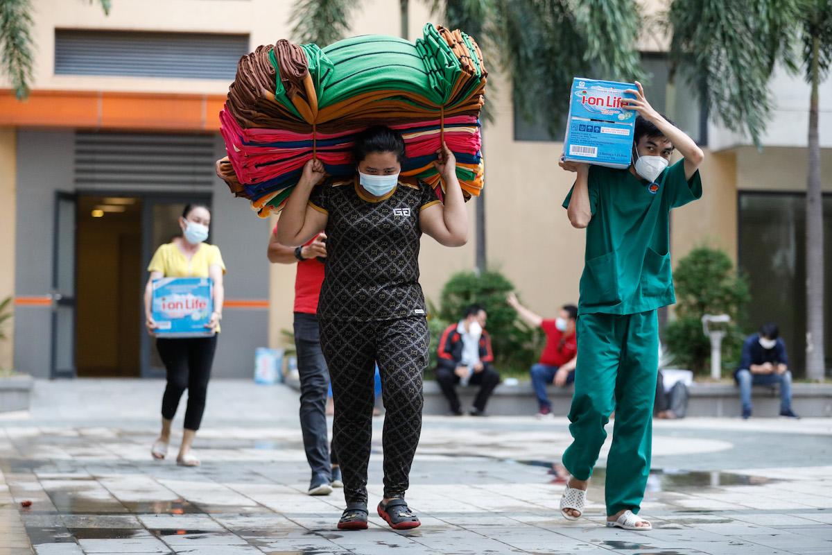 Các nhân viên mang chăn mền, nước vào bệnh viện dã chiến để cấp phát cho bệnh nhân. Ảnh: Hữu Khoa