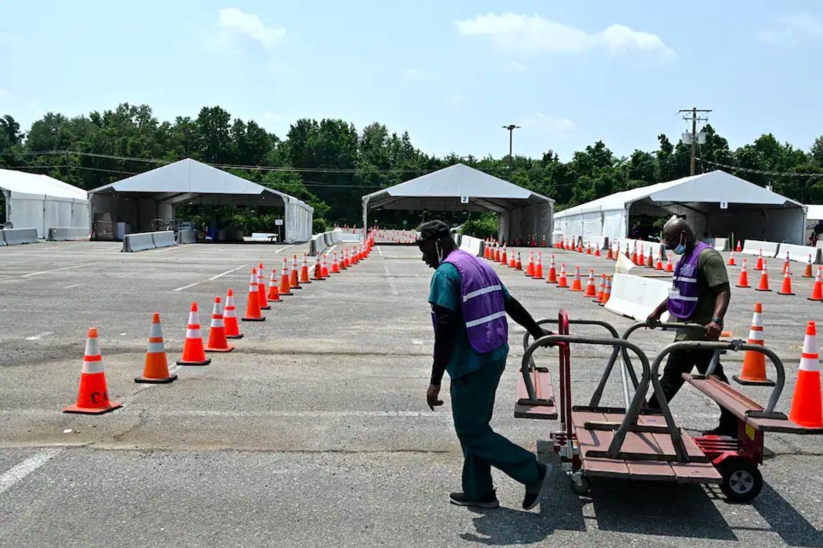 Nhân viên tại điểm tiêm chủng Six Flags tháo dỡ các lều lưu đông, ngày 6/7. Ảnh: Washington Post