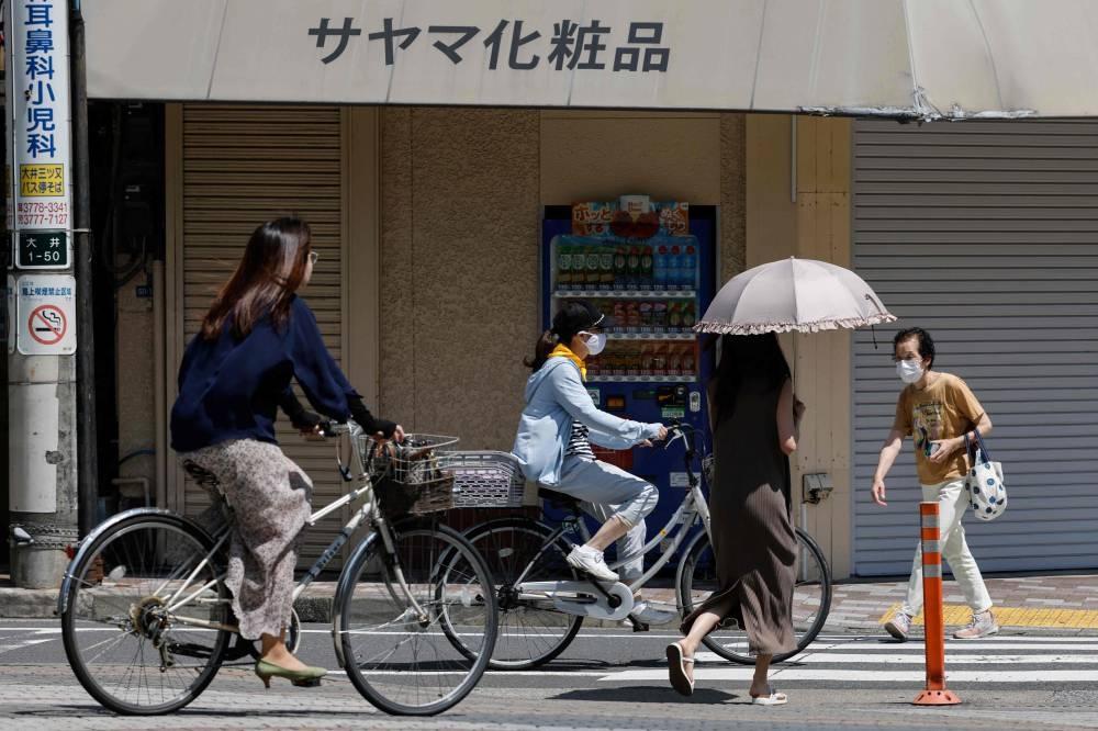 Người Nhật Bản đạp xe tại quận Shinagawa, Tokyo, ngày 19/7. Ảnh: AFP