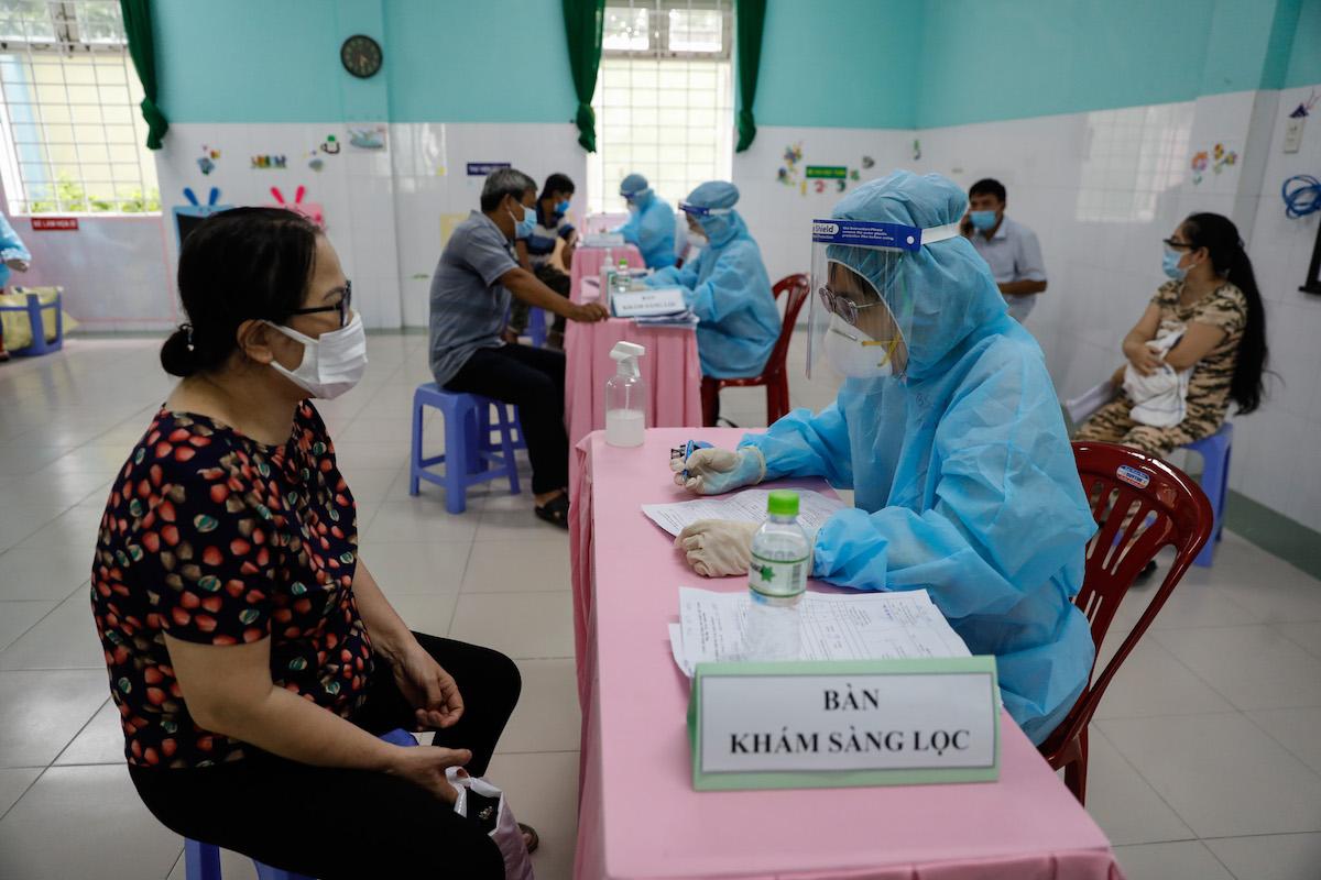 Một người dân khám sàng lọc trước khi tiêm vaccine Covid-19. Ảnh: Hữu Khoa