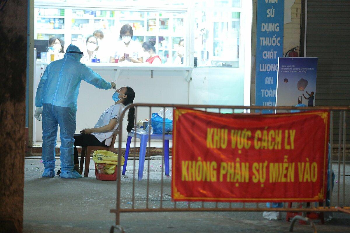 Nhân viên nhà thuốc Đức Tâm, 95 Láng Hạ, lấy mẫu xét nghiệm đêm 19/7. Ảnh: Đặng Thủy.