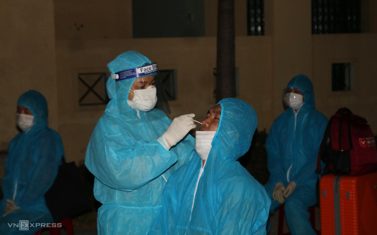 Nhân viên y tế Quảng Nam lấy mẫu xét nghiệm cho người về từ TP HCM rạng sáng 23/7. Ảnh: Đắc Thành.