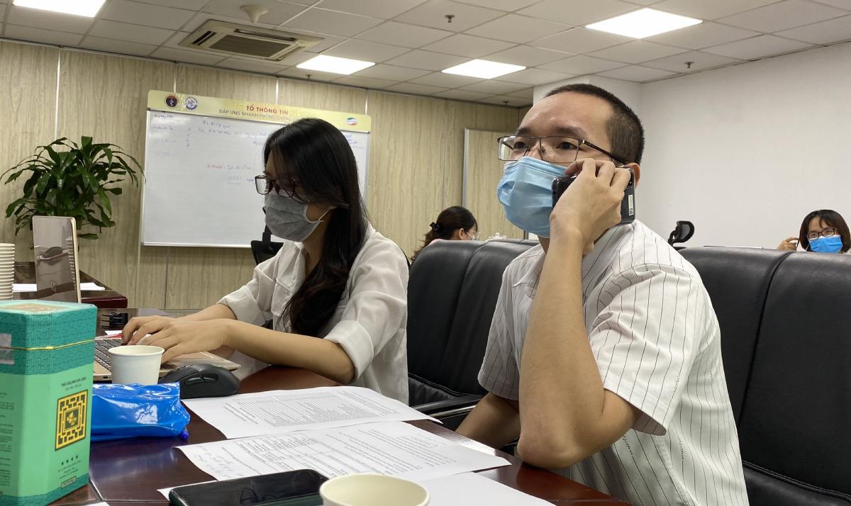 Bác sĩ Bùi Thanh Phúc, Bệnh viện Hữu nghị Việt Đức (bìa phải) đang gọi điện tư vấn cho một bệnh nhân Covid-19 TP HCM chiều 26/7. Ảnh: Bạch Dương.