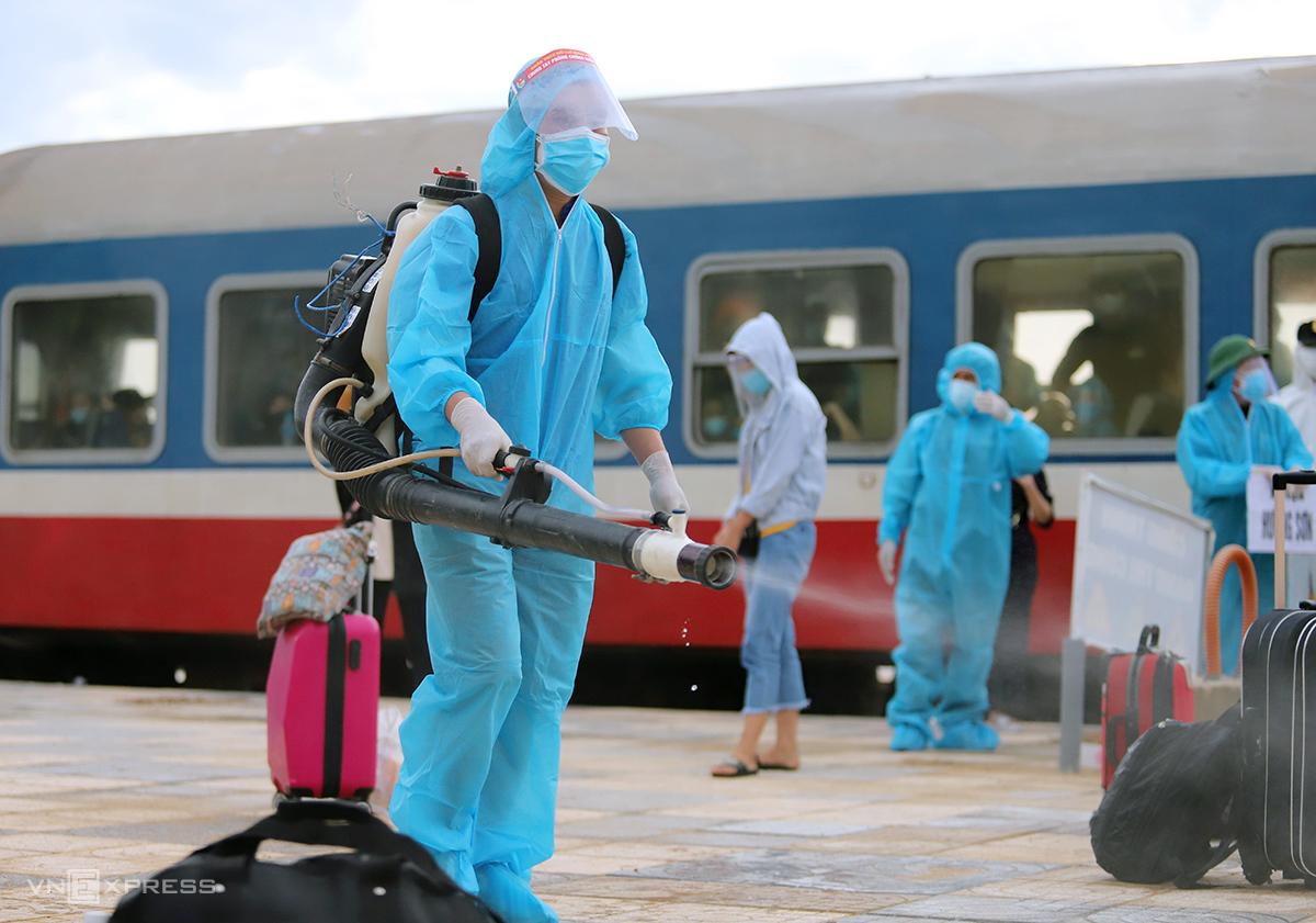 Nhà chức trách phun khử khuẩn hành lý của hành khách tàu SE14, sáng 26/7. Ảnh: Đức Hùng