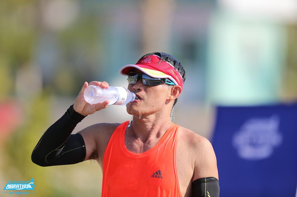 Một vận động viên tiếp nước trên đường chạy VM Quy Nhơn 2020. Ảnh: VnExpress Marathon.