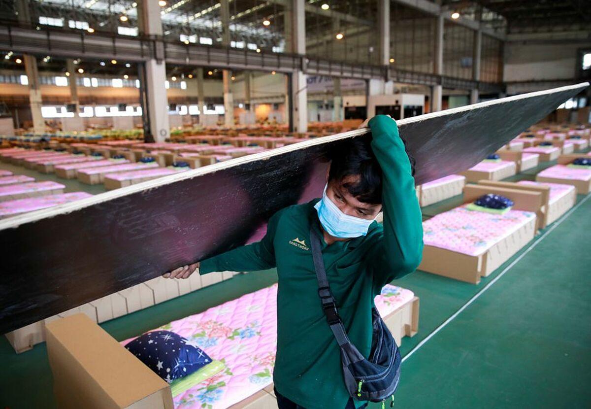 Công nhân bắt đầu xây dựng bệnh viện dã chiến tại kho chứa hàng ở sân bay Don Mueang ở Bangkok, ngày 28/7. Ảnh: Reuters