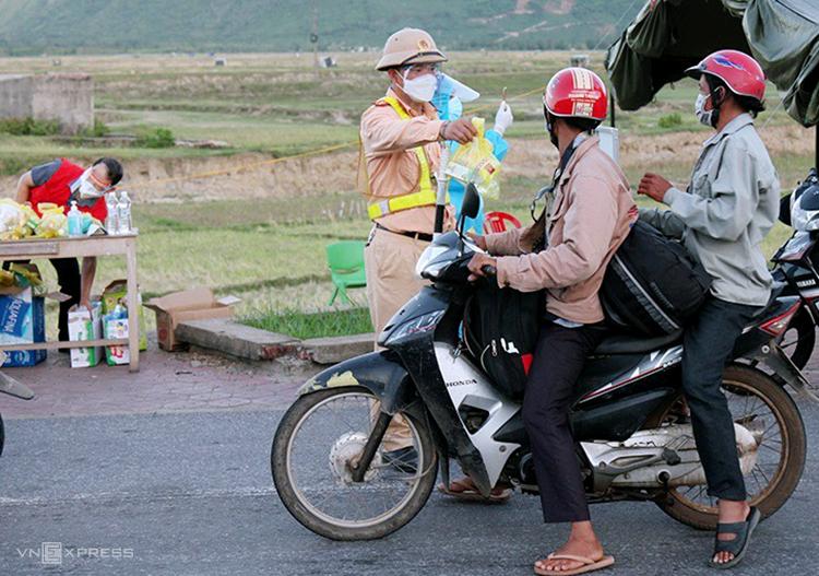 Người đi xe máy từ các tỉnh phía Nam về Hà Tĩnhd dược cảnh sát tiếp tế đồ ăn. Ảnh: Hùng Lê
