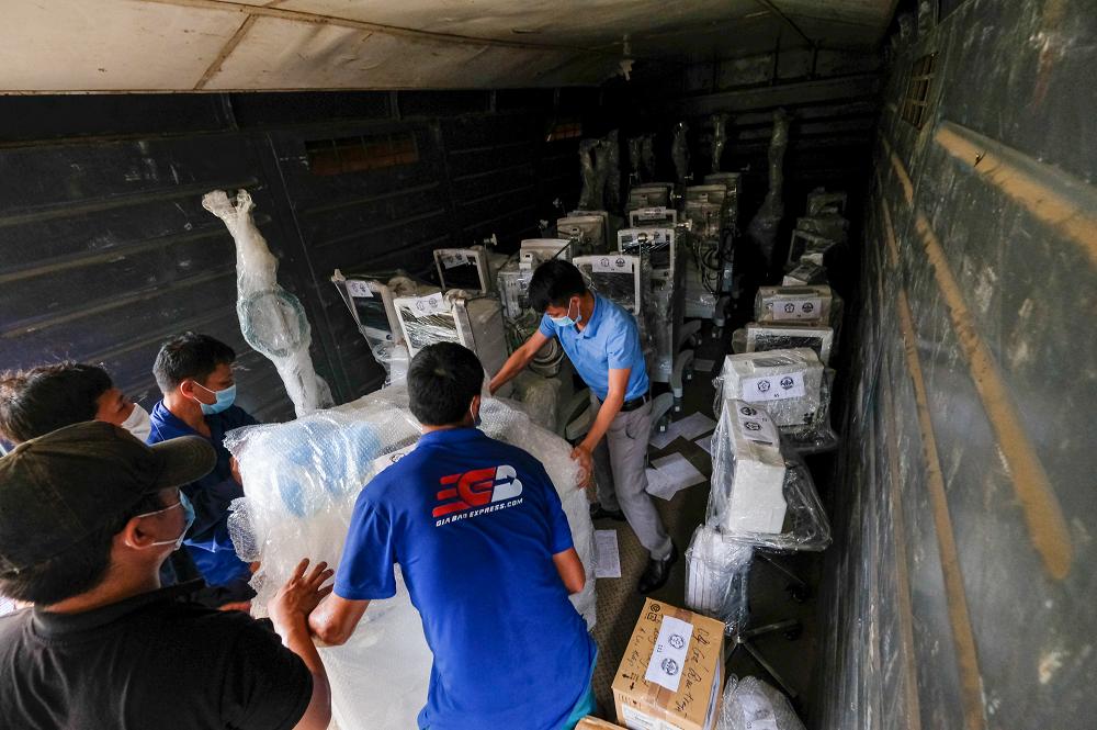 Nhân viên bệnh viện Bạch Mai chuyển thiết bị y tế lên tàu chiều 31/7. Ảnh: Phạm Chiểu.