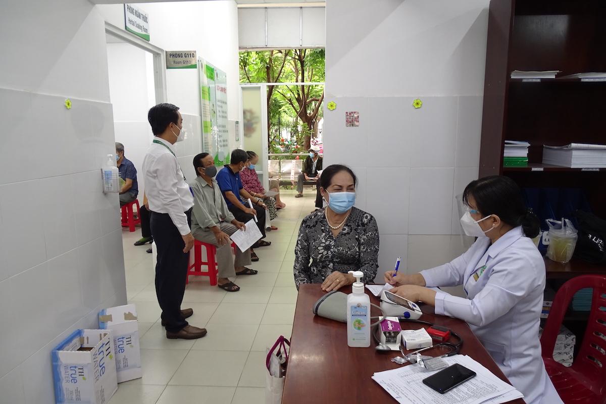 Bác sỹ khám sàng lọc cho người cao tuổi tại hành lang bệnh viện Lê Văn Thịnh trước khi vào tiêm. Ảnh: Hà An