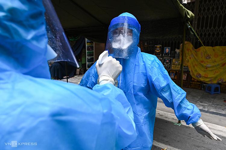 Nhân viên y tế phun khử khuẩn để đảm bảo an toàn sau khi đã lấy mẫu cho người dân phố Hàng Mắm. Ảnh: Giang Huy