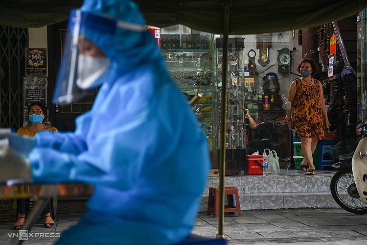 Nhiều người dân Hà Nội đứng ở cửa chờ nhân viên y tế lấy mẫu xét nghiệm. Ảnh: Giang Huy
