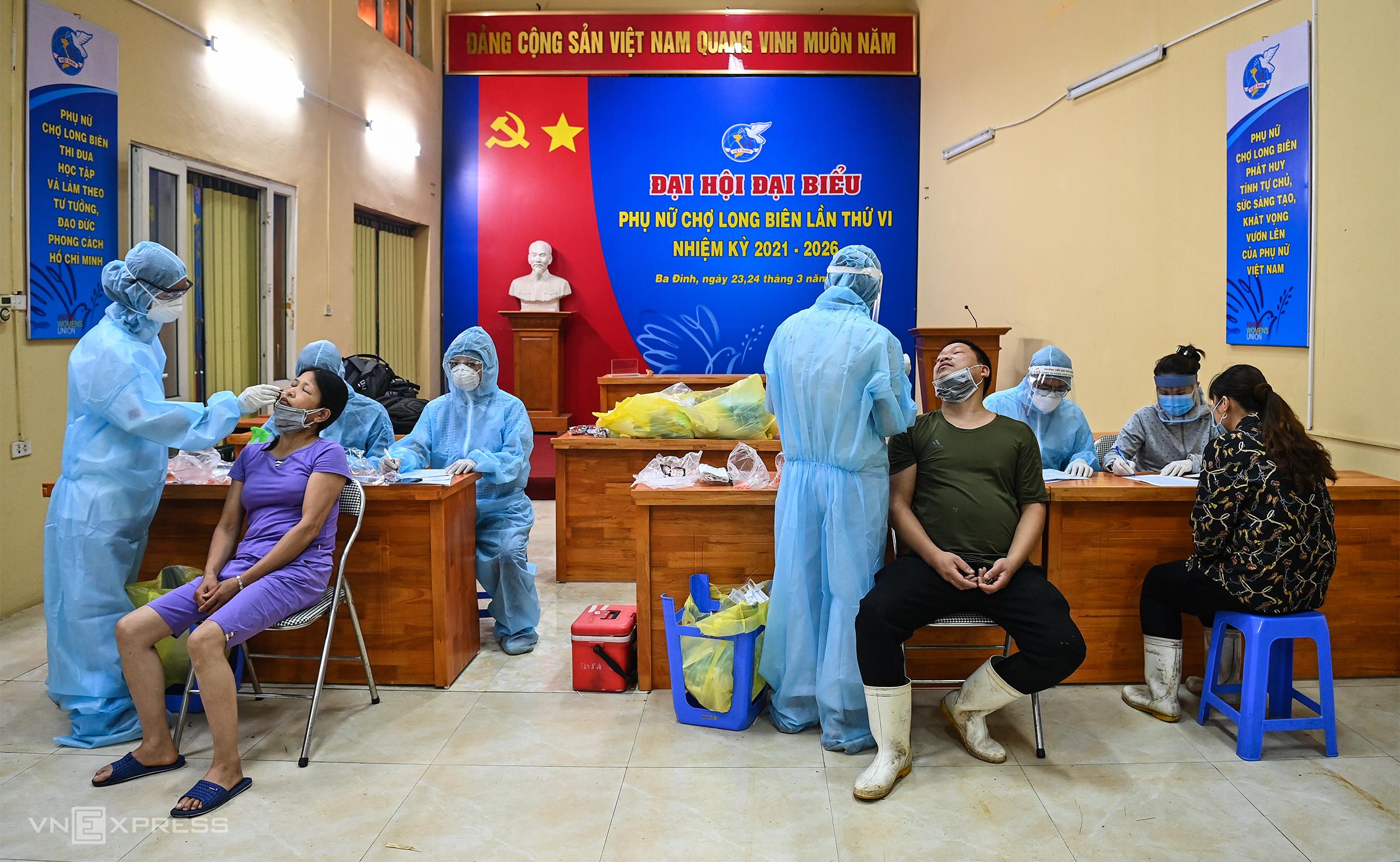 Tiểu thương chợ Long Biên được lấy mẫu xét nghiệm đêm 1/8. Ảnh: Giang Huy.