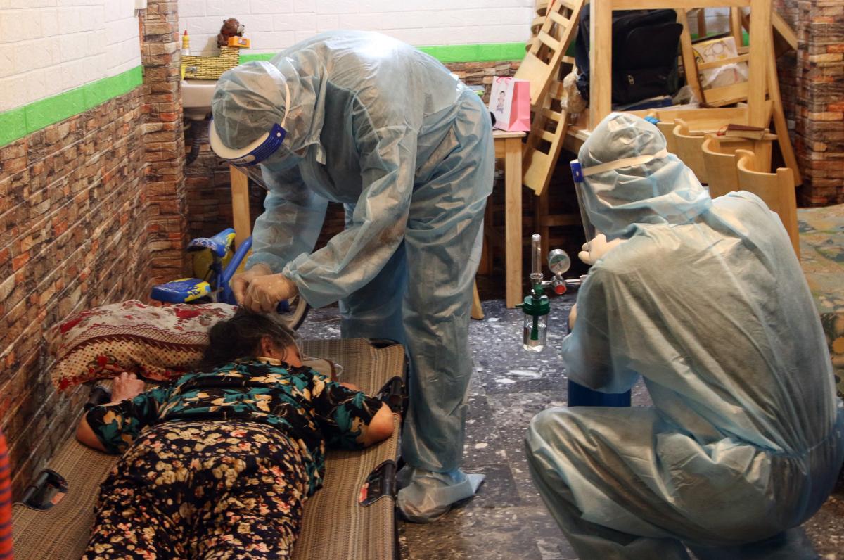 Hai bác sĩ thuộc trạm y tế lưu động số 1, phường 6, quận Tân Bình hướng dẫn một F0 suy hô hấp nằm sấp và cho thở oxy. Ảnh: Thư Anh