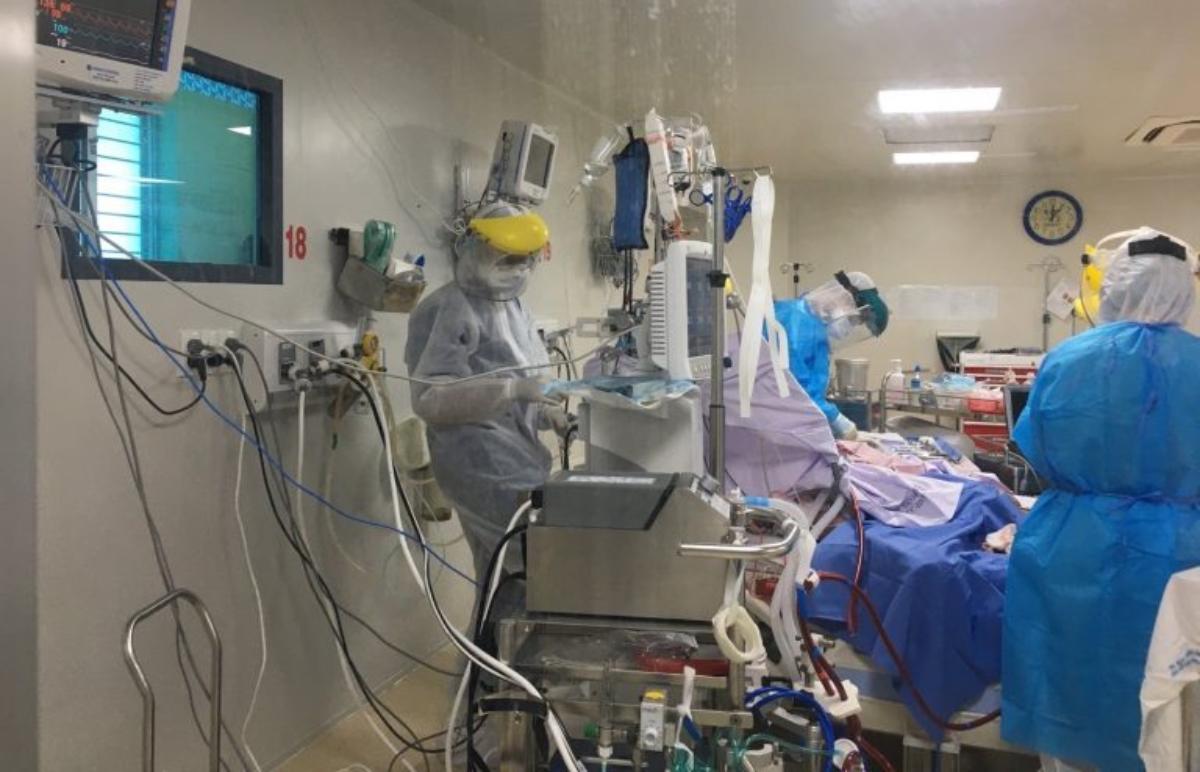 Bệnh nhân 2983, nữ, 65 tuổi, có bệnh nền tiểu đường, tăng huyết áp từng diễn biến nguy kịch, phổi trắng xoá chỉ còn 10-20% khả năng hoạt động, phải chuyển cấp cứu từ An Giang đến TP HCM điều trị. Trong ảnh, các bác sĩ Bệnh viện Bệnh nhiệt đới đang hồi sức tích cực cho bệnh nhân. Hiện bà đã được cai ECMO, dần hồi phục sức khoẻ. Ảnh: Bệnh viện cung cấp.