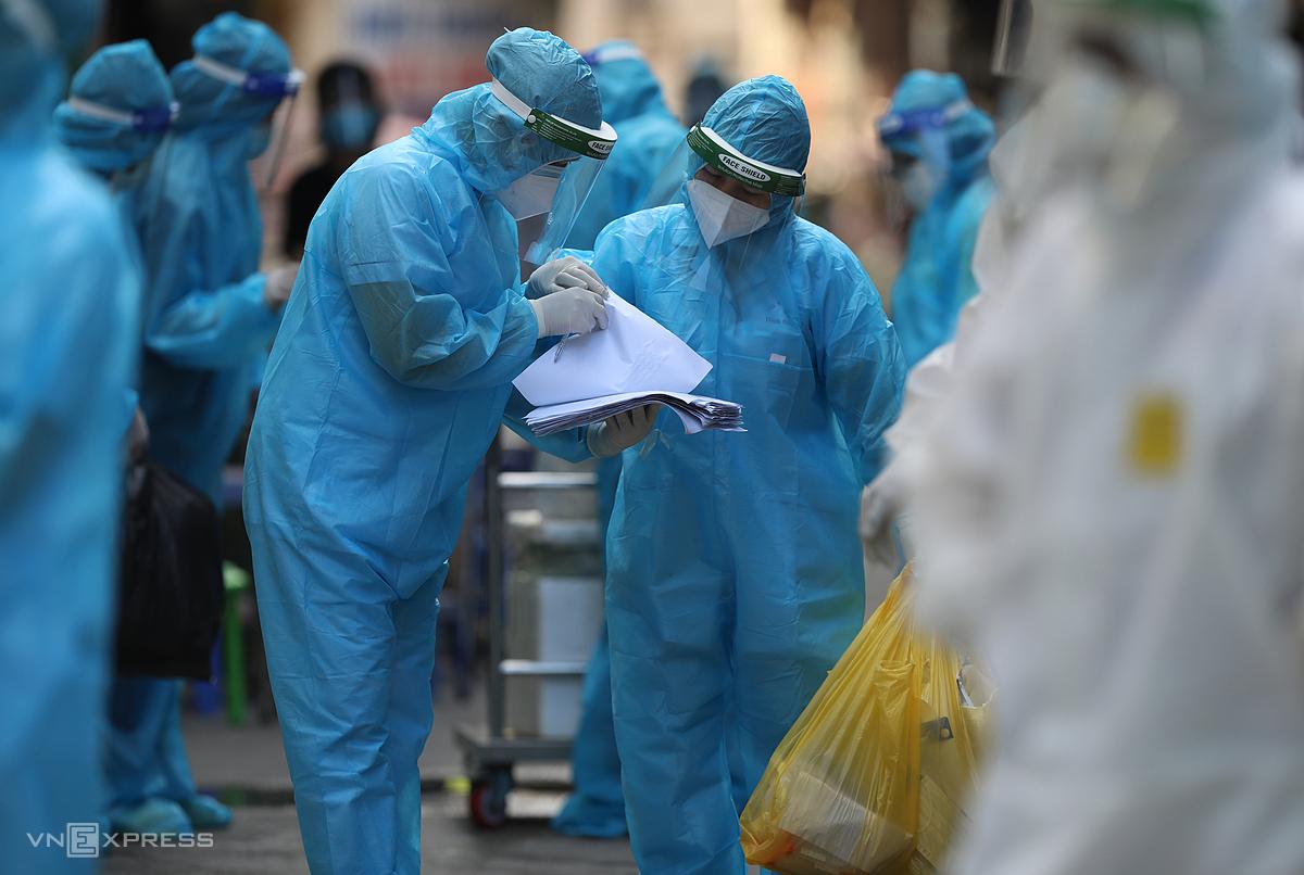Lực lượng y tế cầm danh sách lấy mẫu xét nghiệm cho người dân tại phường Thanh Xuân Trung, quận Thanh Xuân, hôm 26/8. Ảnh: Ngọc Thành.