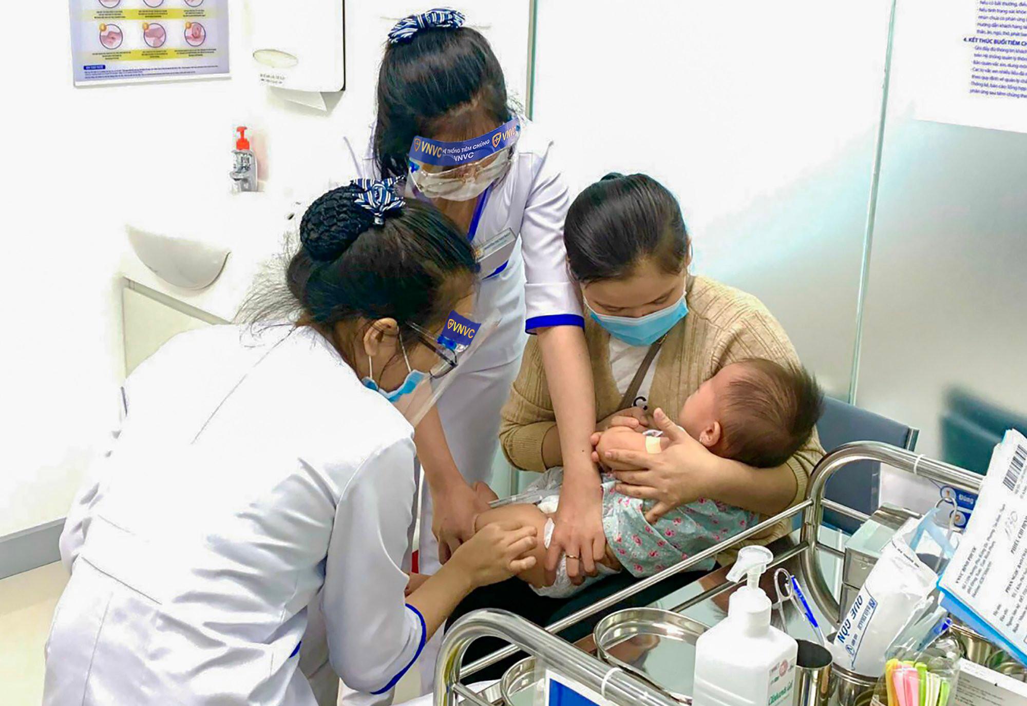 Một phụ huynh đưa trẻ đi tiêm chủng tại Trung tâm Tiêm chủng VNVC Bình Phước. Ảnh: Phong Lan